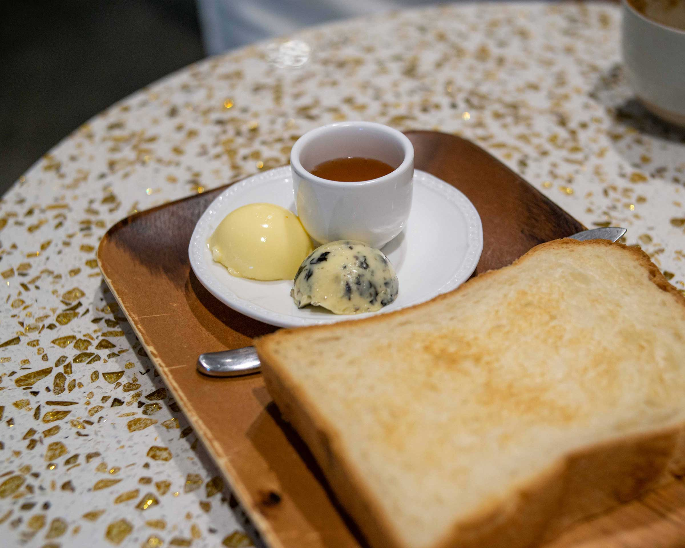 Fat white bread served with honey, unsalted butter and seaweed butter